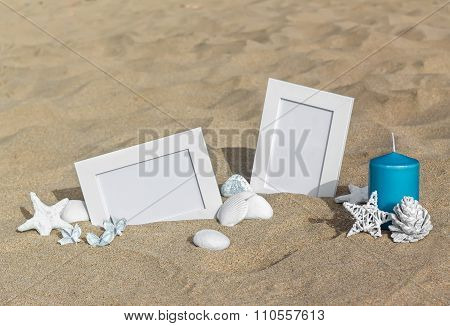 Two blank photo frames on the sand beach with decoration