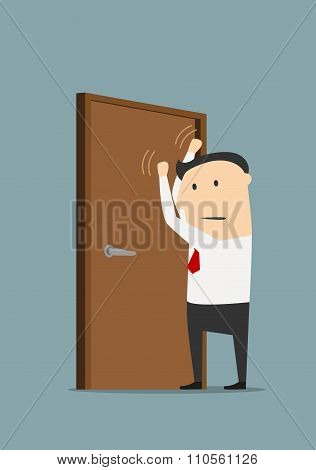 Businessman knocking on a closed door