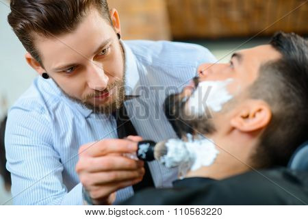Professional barber shaving the beard of his client