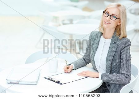 Pretty business woman signing papers
