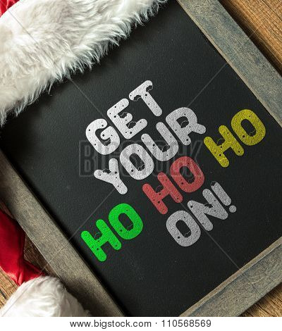 Get Your Ho Ho Ho On! written on blackboard with santa hat
