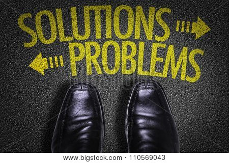 Top View of Business Shoes on the floor with the text: Solutions - Problems