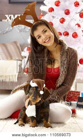 Funny christmas photo with happy woman in reindeer antler and dog in hat.