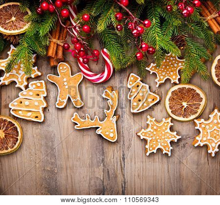 Christmas Holiday Background with various Gingerbread cookies, Candy Cane and evergreens border over wooden table. Christmas and New year food. Christmas decoration and sweets on wood background