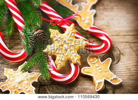 Christmas Holiday Background with Gingerbread cookies, Candy Cane and evergreens border over wooden table. Christmas and New year food. Christmas decoration and sweets on wood background