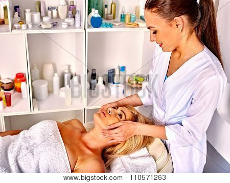 Woman middle-aged take face and neck massage in spa salon. The background shelves cosmetics