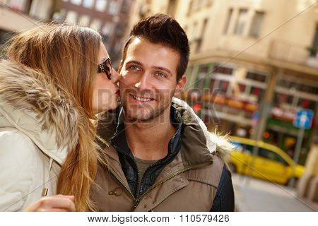 Closeup photo of kissing couple in the city, smiling happy.