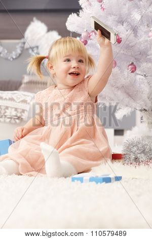 Little girl playing with mobilephone under christmas tree.