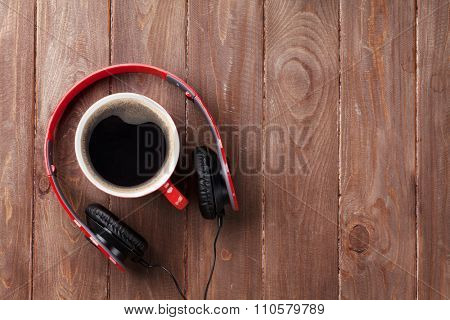 Headphones and coffee cup on wooden desk table. Music concept. Top view with copy space