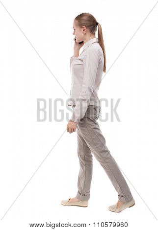 side view of a woman walking with a mobile phone. back view ofgirl in motion.  backside view of person. Isolated over white background. A girl in a white jacket walking slowly pressed phone to his ear