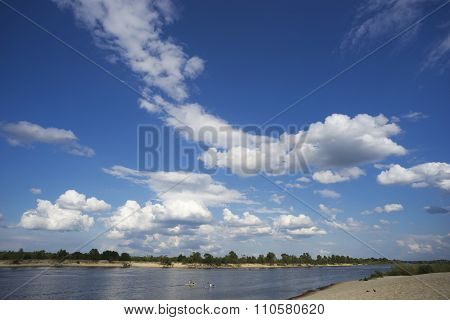 White-winged Clouds On  Sky And Two Kayaks Float Away Into Distance In The River.