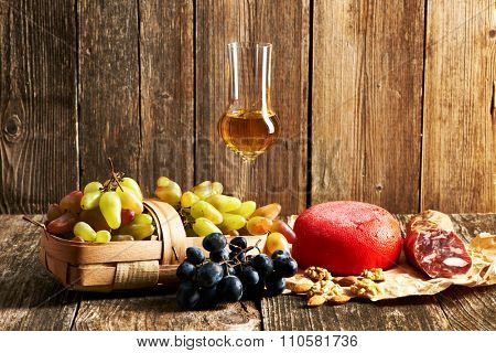 Fresh grapes, grappa and cheese on old wooden table