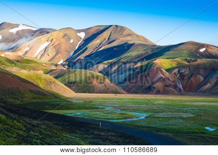 Snow lies in the hollows of colorful rhyolite mountains. Green Valley is flooded with melt water.  Early summer morning in the National Park Landmannalaugar, Iceland