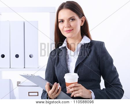 Businesswoman with folders and cup of coffee, standing in office