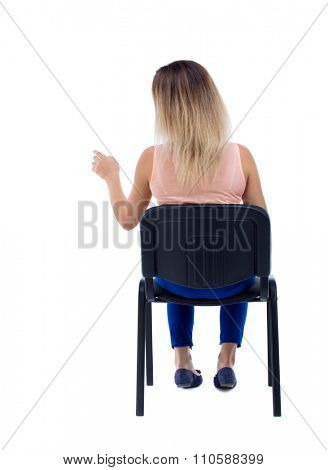 back view young beautiful  woman sitting on chair and pointing.  girl  watching. Rear view people collection. Isolated over white background. girl is sitting on an office chair and presses his finger