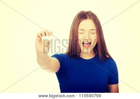 Shocked teenage woman holding pregnancy test.