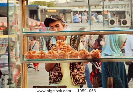 Sweets On Street Food Stall With Vendor In The Traditional Turkish Clothes
