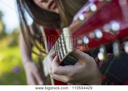 Hands of a young girl on the frets of acoustic guitar.