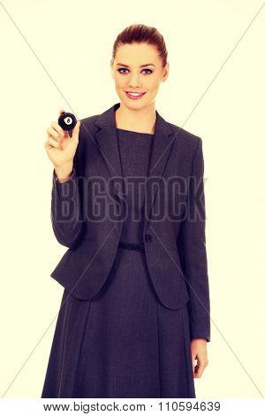 Happy businesswoman holding eight billiard ball.