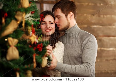 Young Couple In Love Decorates A Christmas Tree At Home