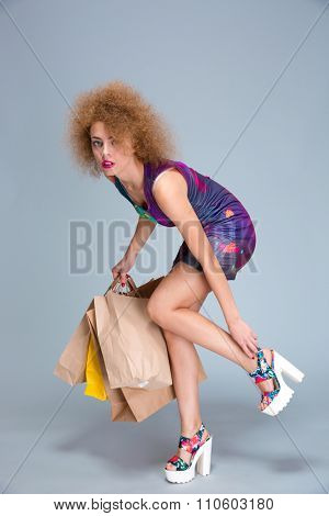 Exhausted tired fatigue young curly woman touching her hurting legs on shopping and holding many shopping bags