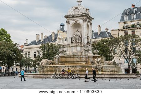 Pedestrians, Bicycles, And Pigeons By The Fontaine Saint Sulpice, Paris