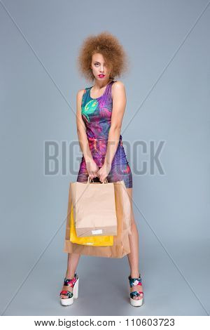 Elegant curly consentrated confident young woman in colorful dress and platform summer shoes posing with many shopping bags