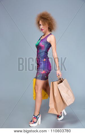 Concentrated beautiful attractive gorgeous curly woman in colorful dress and platform summer shoes walking with paperbags after shopping