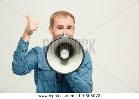 Portrait of a happy man with megaphone showing thumb up isolated on a white background