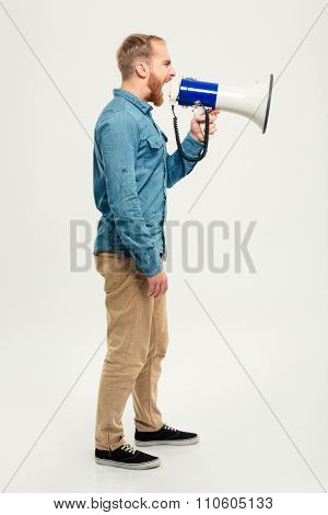 Side view portrait of a casual man screaming in megaphone isolated on a white background