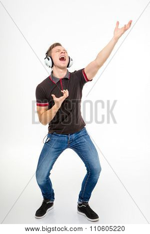 Handsome playful young male in black t-shirt and jeans listening to music using headphones, singing and dancing over white background