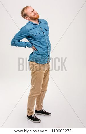 Full length portrait of young handsome male with beard having a backache isolated over white background