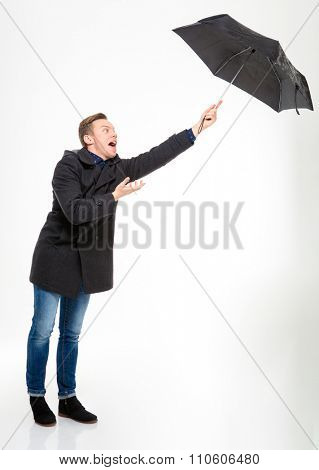 Anxious stressed young man in black coat and jeans with umbrella flying away over white background