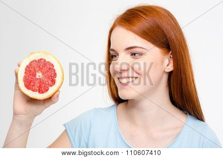 Smiling young happy redhead female looking on half of grapefruit isolated over white background