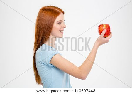 Side view portrait of a happy redhead woman holding red apple isolated on a white background