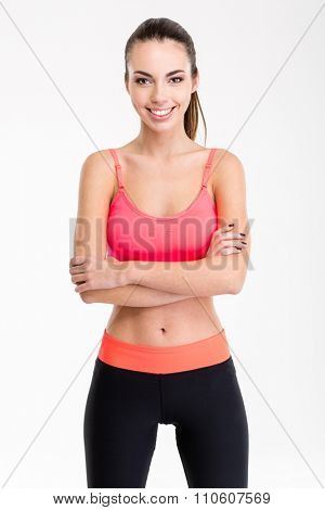 Beautiful smiling young sportswoman in pink top and black   leggings standing with crossed arms isolated over white background