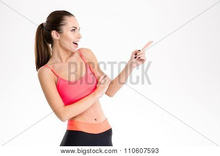 Excited content pretty fitness girl in sportwear pointing away and looking away over white background