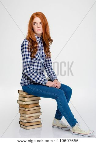 Thoughtful beautiful curly young woman with long red hair in checkered shirt and jeans sitting on books and thinking over white background