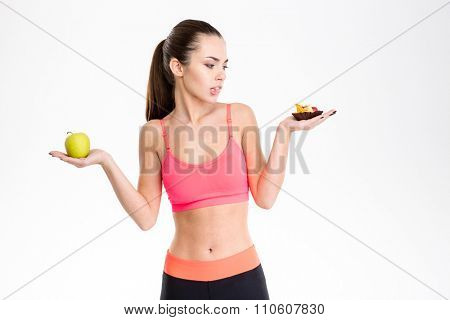 Portrait of tempted attractive fitness woman making food choice isolated over white background