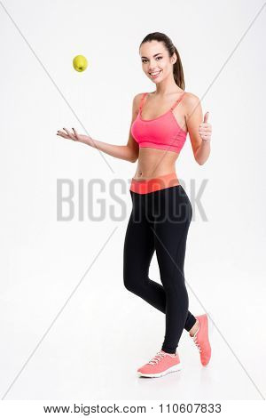 Full length of attractive cheerful young fitness woman in pink top and black leggings throwing up an apple and showing thumbs up over white background