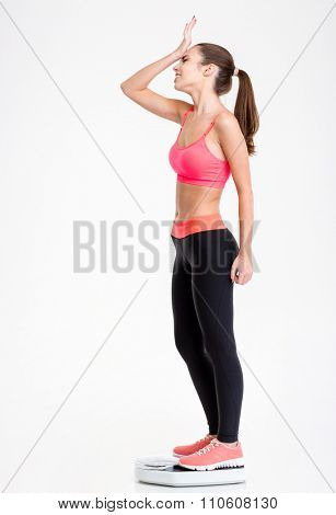 Full length of upset disappointed fitness girl standing on weighing scale over white background