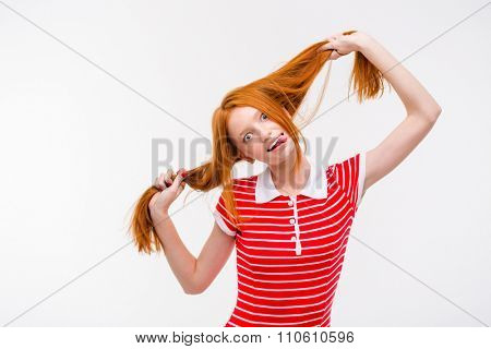 Amusing redhead positive funny young woman showing tongue and having fun posing over white background