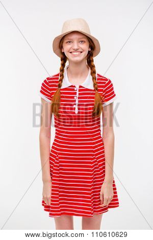 Portrait of amusing positive redhead girl with two braids in boonie hat and casual dress posing on white background