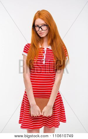 Cute shy young woman in glasses with long red hair standing and holding a book on white background