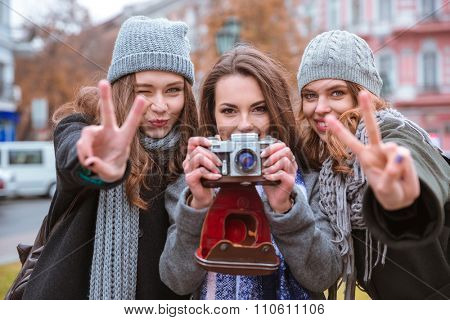 Portrait of a happy three women making photo on camera outdoors