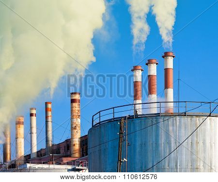 Industrial Smoking Chimneys Against The Blue Sky