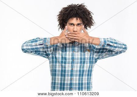 Portrait of a serious afro american man covering his mouth with palms isolated on a white background