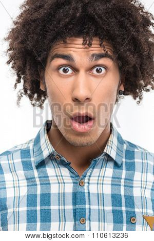 Portrait of a shocked afro american man with curly hair looking at camera isolated on a white background