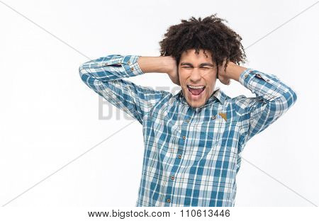 Portrait of a young afro american man covering his ears and screaming isolated on a white background