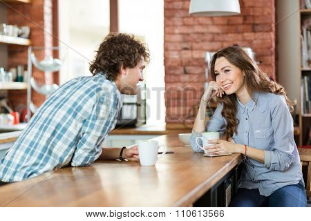 Young beautiful happy couple enjoying coffee in cafeteria